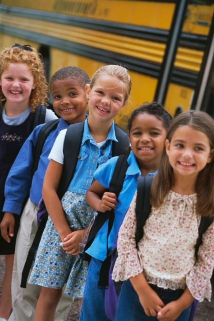 Smiling Children by School Bus